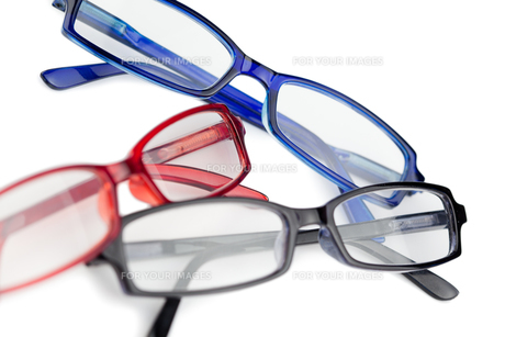 Three pairs of spectacles with blue red and black frames FYI00487761