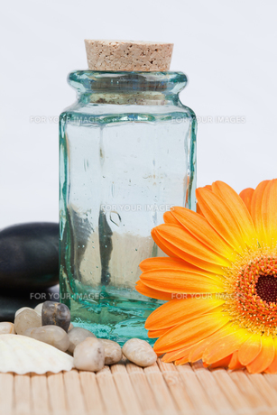 A glass flask with round smooth pebbles and a sunflower FYI00487813
