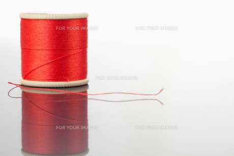 Red spool of thread on a table FYI00487918