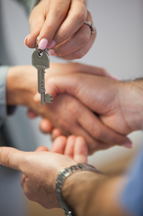 Estate agent giving house key to customer while shaking hands FYI00488119