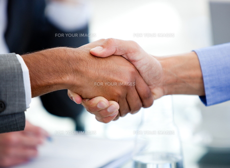 Close up of business partners shaking hands FYI00488249