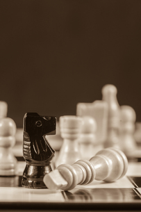 Fallen white chess piece lying next to black knight in sepia tone FYI00488362