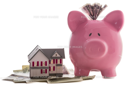 Close up of a pink piggy bank with dollars beside miniature house model FYI00488391