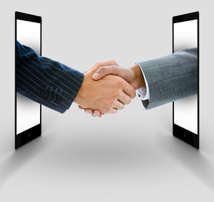 Businessmen shaking hands from digital tablets FYI00488657
