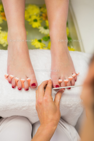 Woman polishing toe nails at spa center FYI00488670