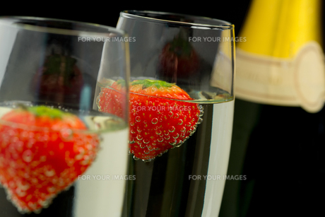 Strawberries floating in two champagne flutes FYI00488758