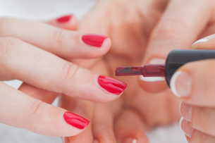 Details shot of hands applying red nail varnish to nails FYI00488762