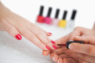 Woman applying nail varnish to finger nails FYI00488802