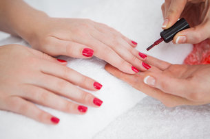 Woman applying nail varnish to finger nails FYI00488819