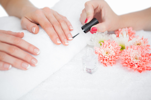 Woman applying nail varnish to finger nails FYI00488828