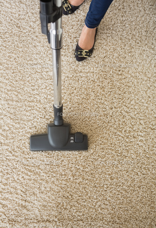 Carpet being hoovered by woman FYI00488854