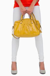 Woman in white leggings holding yellow bag FYI00488925