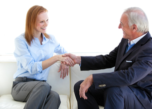 Young business people shaking hands in agreement FYI00488948