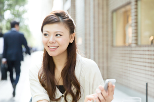 カフェで携帯電話を使う女性 FYI00490737