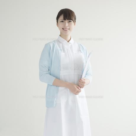 カルテを持ち微笑む看護師の素材 [FYI00491250]