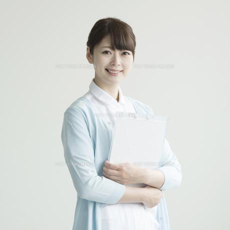 カルテを持ち微笑む看護師 FYI00491253
