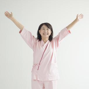 両手を広げ微笑む患者 FYI00491261