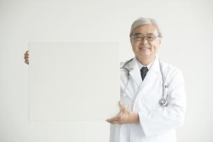 メッセージボードを持ち微笑む医者 FYI00491277