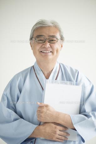 カルテを持ち微笑む患者 FYI00491288