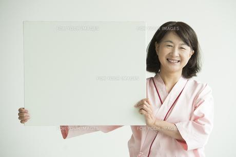 メッセージボードを持ち微笑む患者 FYI00491289
