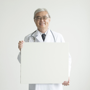 メッセージボードを持ち微笑む医者 FYI00491290
