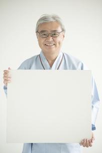 メッセージボードを持ち微笑む患者 FYI00491295