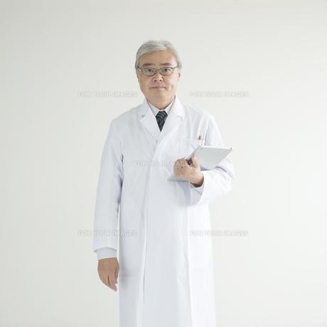タブレットPCを持ち真剣な表情をする医者 FYI00491312