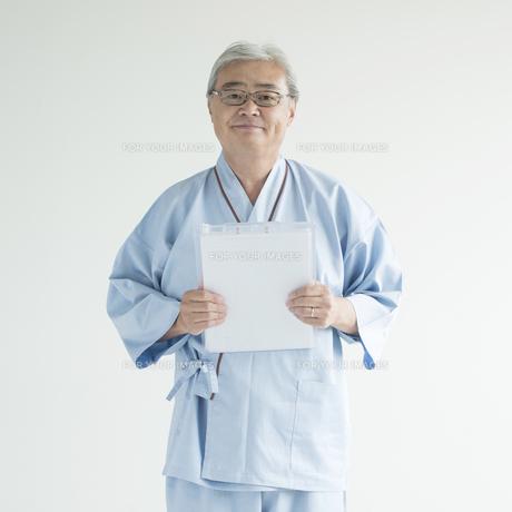 カルテを持ち微笑む患者 FYI00491360