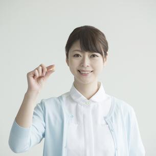 薬を持ち微笑む看護師 FYI00491383