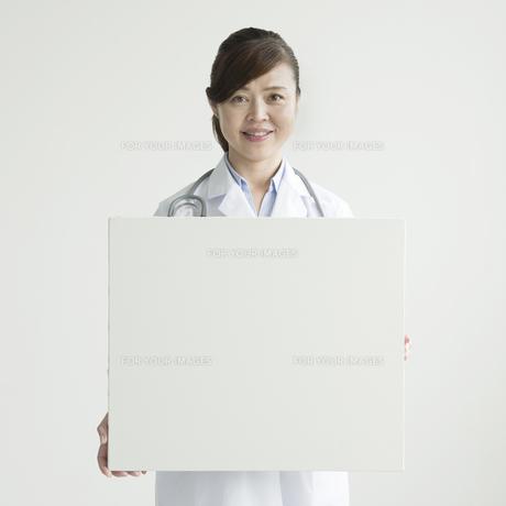 メッセージボードを持ち微笑む女医 FYI00491408