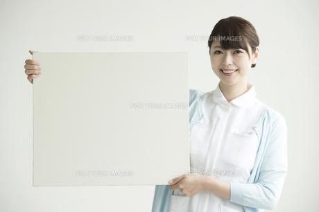メッセージボードを持ち微笑む看護師 FYI00491413