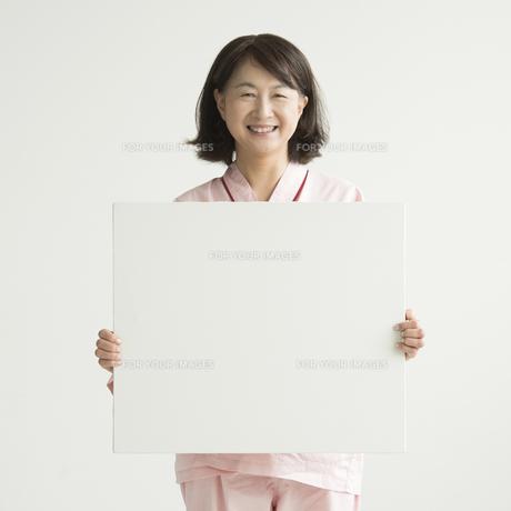 メッセージボードを持ち微笑む患者 FYI00491417