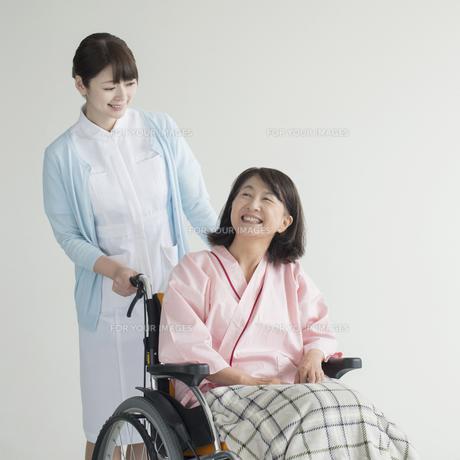 車椅子に乗る患者と話をする看護師 FYI00491419