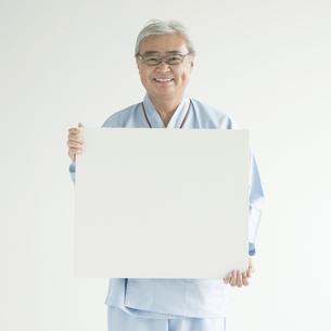 メッセージボードを持ち微笑む患者 FYI00491420