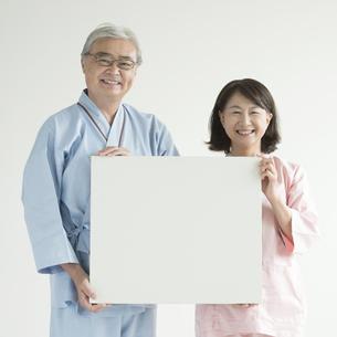 メッセージボードを持ち微笑む患者 FYI00491445