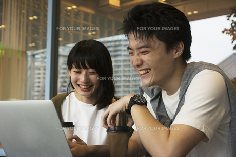 カフェでパソコンを見るカップルの素材 [FYI00491505]