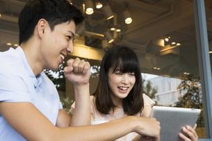 カフェでタブレットを使うカップル FYI00491513