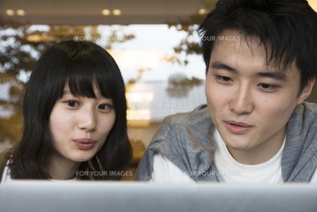 カフェでパソコンを見るカップル FYI00491515