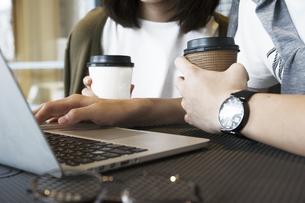 カフェでパソコンを見るカップルの素材 [FYI00491518]