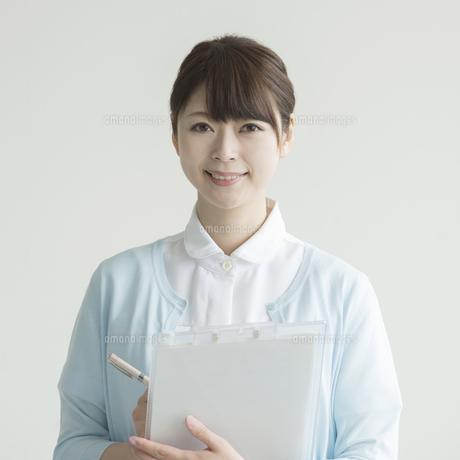 カルテを持ち微笑む看護師 FYI00491782