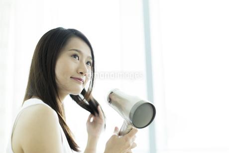 ドライヤーで髪を乾かす若い女性 FYI00497338
