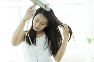 ドライヤーで髪を乾かす若い女性 FYI00497343