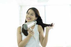 ドライヤーで髪を乾かす若い女性 FYI00497346