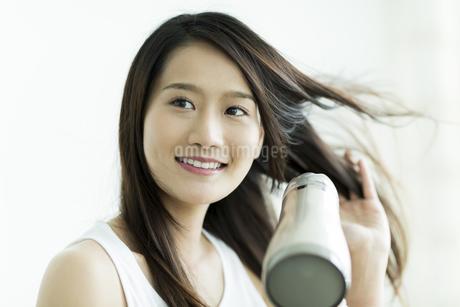 ドライヤーで髪を乾かす若い女性 FYI00497357