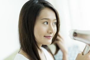 ドライヤーで髪を乾かす若い女性 FYI00497358