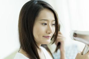 ドライヤーで髪を乾かす若い女性 FYI00497363