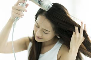 ドライヤーで髪を乾かす若い女性 FYI00497365