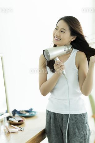 ドライヤーで髪を乾かす若い女性 FYI00497366