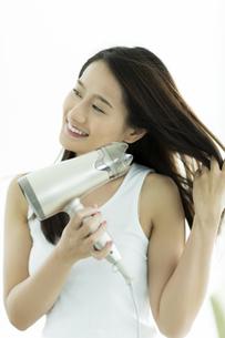 ドライヤーで髪を乾かす若い女性 FYI00497367