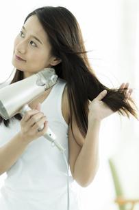 ドライヤーで髪を乾かす若い女性 FYI00497370